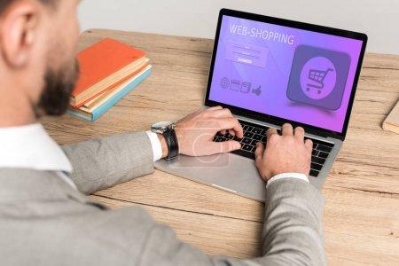 Photo pour Vue recadrée de l'homme d'affaires à l'aide d'un ordinateur portable avec site web shopping à l'écran isolé sur gris - image libre de droit