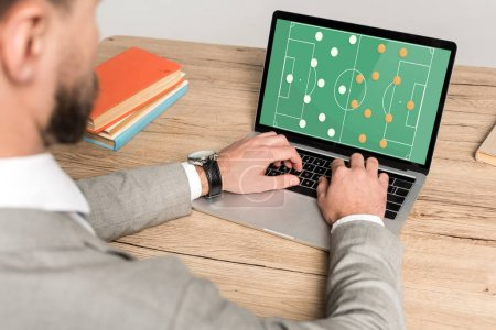 Photo for Cropped view of businessman playing football video game on laptop isolated on grey - Royalty Free Image