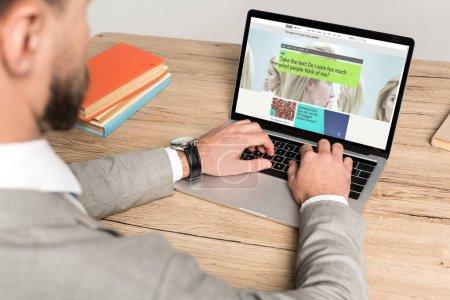 KYIV, UKRAINE - 25 NOVEMBRE 2019 : vue recadrée d'un homme d'affaires utilisant un ordinateur portable avec le site Web de BBC Science à l'écran isolé sur gris