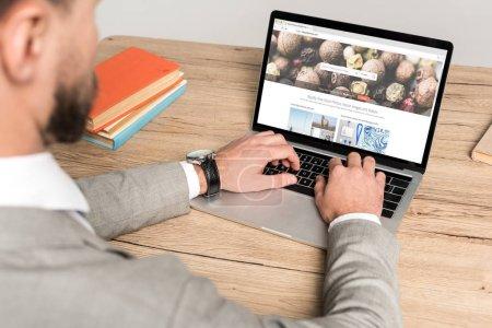 Photo pour KYIV, UKRAINE - 25 NOVEMBRE 2019 : vue recadrée d'un homme d'affaires utilisant un ordinateur portable avec le site Depositphotos à l'écran isolé sur gris - image libre de droit