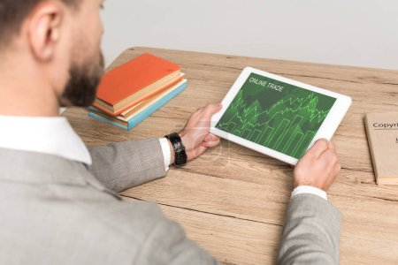 Photo for Cropped view of businessman using digital tablet with online trade app on screen isolated on grey - Royalty Free Image