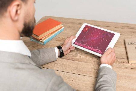 """Photo pour Vue en coupe d'un homme d'affaires utilisant une tablette numérique avec des graphiques et des tableaux à l """"écran isolés en gris - image libre de droit"""