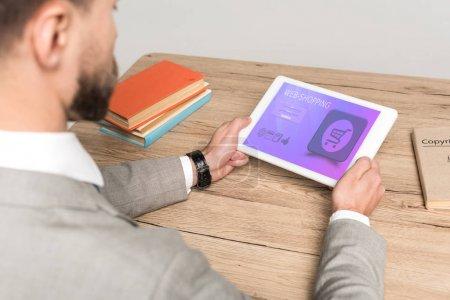 Photo pour Vue partielle de l'homme d'affaires à l'aide d'une tablette numérique avec application web shopping à l'écran isolé sur gris - image libre de droit