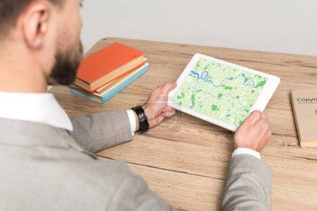 Ausgeschnittene Ansicht des Geschäftsmannes mit digitalem Tablet und Karte auf dem Bildschirm isoliert auf grau