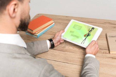 Photo pour Vue partielle d'un homme d'affaires utilisant une tablette numérique avec application d'achat en ligne à l'écran isolée sur gris - image libre de droit