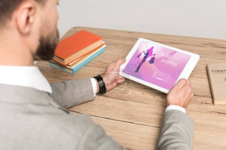 Photo pour Cropping view of business man using digital tablet with online shopping app on screen isolated on grey - image libre de droit