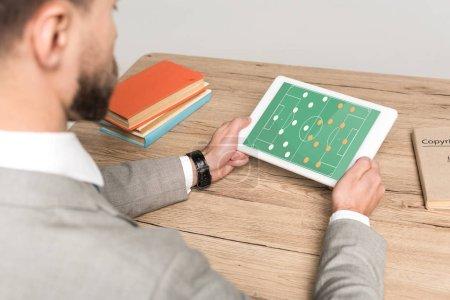 Photo pour Vue recadrée de l'homme d'affaires jouant au football jeu vidéo sur ordinateur portable isolé sur gris - image libre de droit