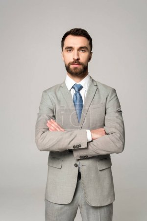 Photo for Serious businessman standing with crossed arms and looking at camera isolated on grey - Royalty Free Image