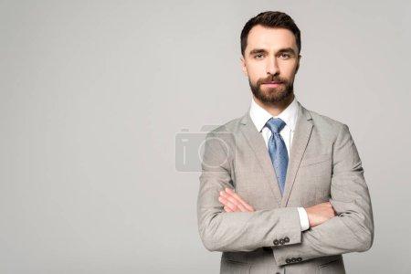 Foto de Un hombre de negocios confiado que se pone de pie con los brazos cruzados y mira la cámara aislada en gris - Imagen libre de derechos