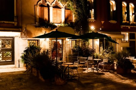 Photo for Outdoor cafe with chairs and tables at night in Venice, Italy - Royalty Free Image