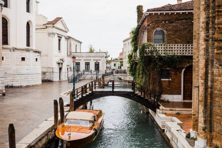motor boat near bridge and ancient buildings in Venice, Italy