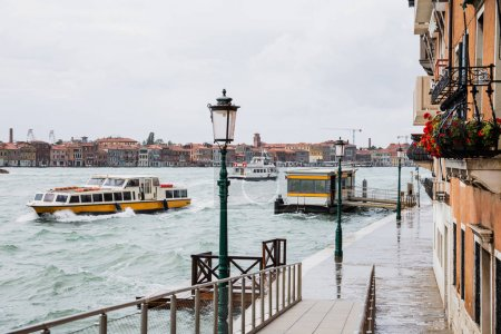 Photo for Vaporettos floating on river near ancient buildings in Venice, Italy - Royalty Free Image