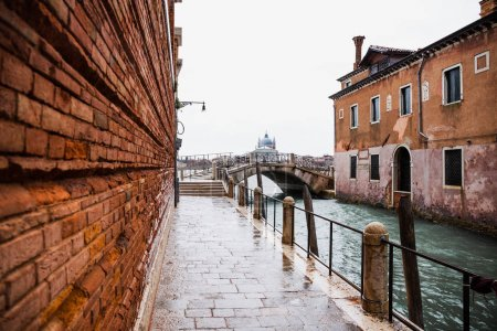 Photo for Road along canal and ancient building in Venice, Italy - Royalty Free Image