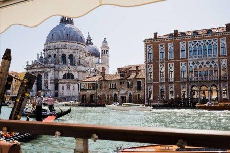 Photo for VENICE, ITALY - SEPTEMBER 24, 2019: motor boats and gondolas floating on canal near Santa Maria della Salute church - Royalty Free Image
