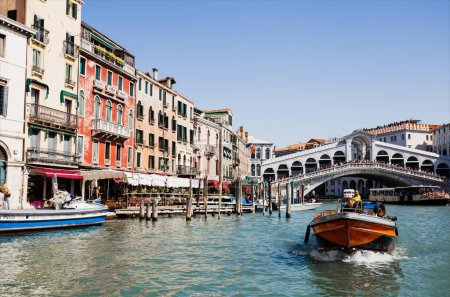 Photo for VENICE, ITALY - SEPTEMBER 24, 2019: Rialto Bridge, ancient buildings and motor boat floating on canal in Venice, Italy - Royalty Free Image