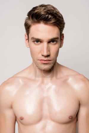 Photo pour Homme sexy avec torse musculaire regardant la caméra isolée sur gris - image libre de droit