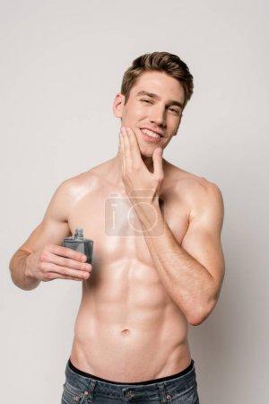 Photo pour Homme sexy souriant avec torse musculaire appliquant après-rasage sur le visage isolé sur gris - image libre de droit