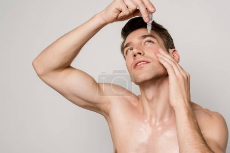 Photo for Sexy man with bare torso using eye drops isolated on grey - Royalty Free Image