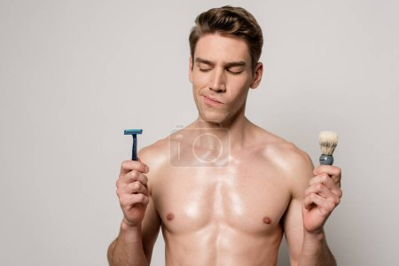 Photo pour Homme sexy réfléchi avec torse musculaire tenant rasoir et brosse à raser isolé sur gris - image libre de droit