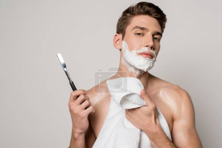 Photo for Sexy man with muscular torso and shaving foam on face holding straight razor and towel isolated on grey - Royalty Free Image