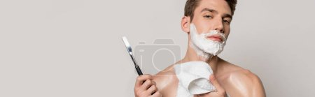 Photo for Sexy man with muscular torso and shaving foam on face holding straight razor and towel isolated on grey, panoramic shot - Royalty Free Image