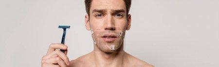 Photo pour Homme sexy avec le torse musculaire et les blessures sanglantes après le rasage tenant rasoir isolé sur gris, plan panoramique - image libre de droit
