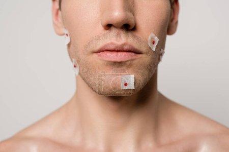 Photo pour Crochet vue d'un homme nu avec des blessures sanglantes après le rasage sur le visage isolé sur gris - image libre de droit