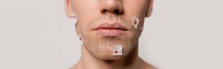 """Photo pour Crochet vue d'un homme nu avec des blessures sanglantes après s """"être rasé le visage isolé sur une photo panoramique grise - image libre de droit"""