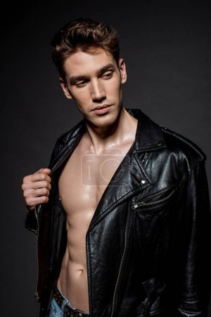 Photo for Sexy young man with muscular torso in biker jacket on black background - Royalty Free Image