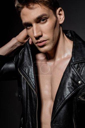 Photo pour Sexy jeune homme avec torse musculaire en veste de motard regardant la caméra sur fond noir - image libre de droit