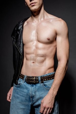 Photo for Cropped view of sexy young man with muscular torso in biker jacket and jeans on black background - Royalty Free Image