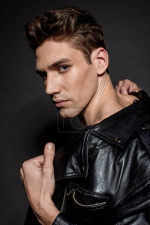 Photo for Sexy young man with muscular torso in biker jacket looking at camera on black background - Royalty Free Image