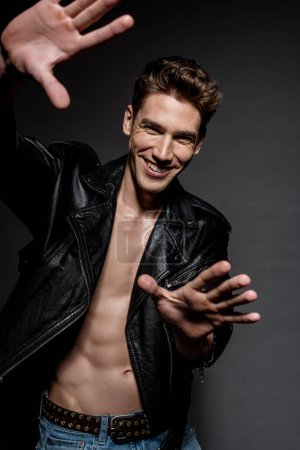 Photo for Selective focus of sexy smiling man with muscular torso in biker jacket and jeans gesturing with hands on black background - Royalty Free Image