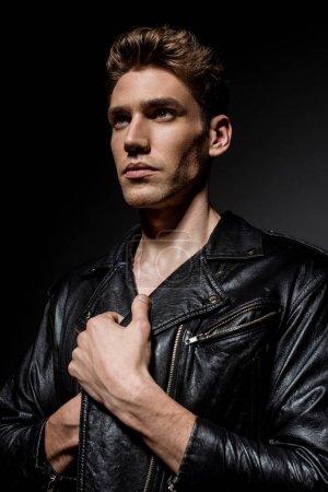 Photo pour Jeune homme sexy vêtu d'une veste de cycliste regardant dehors sur fond noir - image libre de droit