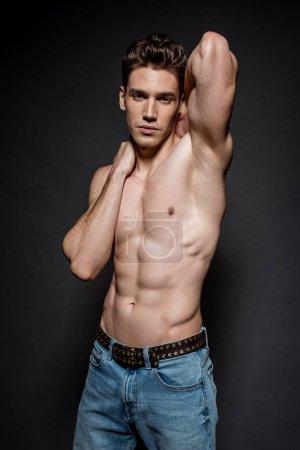 Photo pour Sexy jeune homme avec torse musculaire en jeans posant sur fond noir - image libre de droit