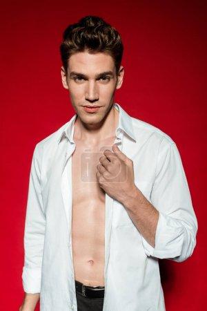 Photo pour Jeune homme sexy et élégant en chemise non boutonnée sur fond rouge - image libre de droit