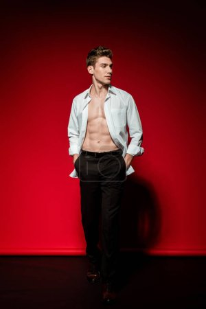 Photo for Sexy young elegant man in unbuttoned shirt with muscular bare torso and hands in pockets on red background - Royalty Free Image