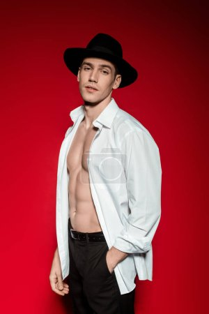 Photo for Sexy young elegant man in unbuttoned shirt and hat with muscular bare torso posing on red background - Royalty Free Image