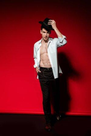 sexy junger eleganter Mann im aufgeknöpften Hemd mit muskulösem nacktem Oberkörper, der einen Hut auf rotem Hintergrund aufsetzt