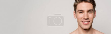 Photo for Smiling sexy man with muscular torso isolated on grey, panoramic shot - Royalty Free Image