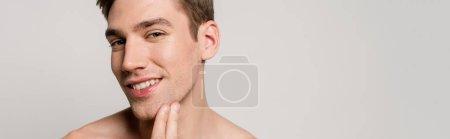 Photo pour Jeune homme souriant, nu et sexy touchant la peau isolé sur fond gris, photo panoramique - image libre de droit