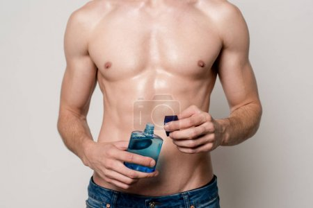 Photo for Cropped view of sexy man with muscular torso with after shave lotion isolated on grey - Royalty Free Image