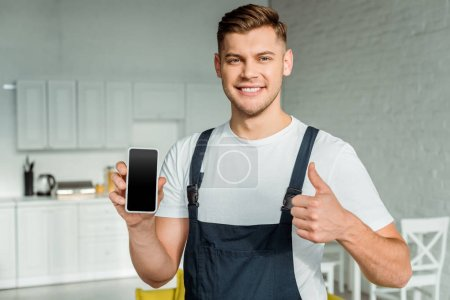 happy installer holding smartphone with blank screen and showing thumb up