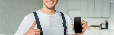 Photo for Panoramic shot of happy installer holding smartphone with blank screen and showing thumb up - Royalty Free Image
