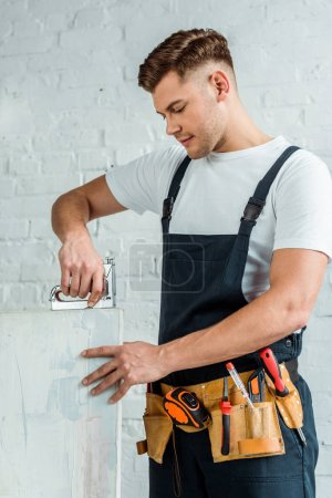 Foto de Handsome installer holding construction stapler near painting - Imagen libre de derechos