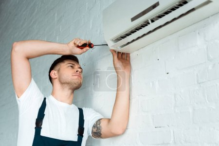 Foto de Handsome tattooed installer holding screwdriver near air conditioning. - Imagen libre de derechos