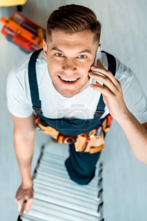 Photo for Top view of happy installer climbing ladder and talking on smartphone - Royalty Free Image