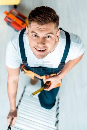 Photo pour Top view d'un installateur heureux grimpant dans une échelle et regardant une caméra - image libre de droit