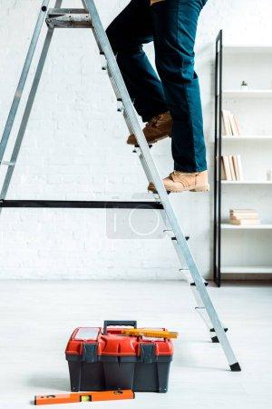 Photo pour Vue en coupe du (de la) travailleur grimpant une échelle près de la boîte à outils - image libre de droit