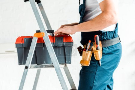 Photo for Cropped view of installer standing on ladder and holding tool box - Royalty Free Image